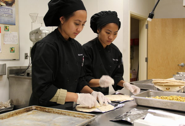 "Juniors Shaina Casio and Phuong Chau wrap burritos that will be served as part of the menu for Coyote Cafe. Coyote Cafe opened on Nov. 25 and will serve breakfast and lunch Tuesdays through Thursdays every week. ""Having to prepare the food for Coyote Cafe was tough, but fun. We had to do multiple things at once in order to finish preparing all the food by lunch time,"" Chau said.  Photo Credit: Helen Abraha"