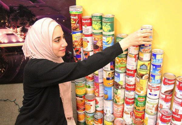 Columnist Summer Thomad re-organizes cans donated by students to contribute to the less-fortunate for the holiday season. Donating non-perishable food items is a great way to show kindness to the less fortunate or those in need.  Photo Credit: Alex Nedelcu