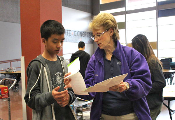 """HOSA member Matthew Le receives a card to buy a gift for a child. All members are encouraged to buy gifts for as many children as they can. """"I wanted to help give back to the community and give a child a toy they have always wanted,"""" Le said. Photo Credit: Nikki Molina"""