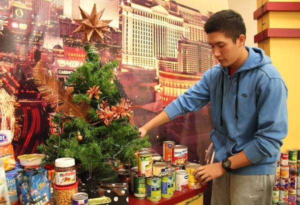 """As food is delivered to the Rout(e) 131 set, junior Jacob Young fixes the cans around the set. 245 food items have been donated as of Dec. 4. """"Donating food is amazing, especially when you're helping people in need,"""" Young said.  Photo Credit: Acel Soriano"""