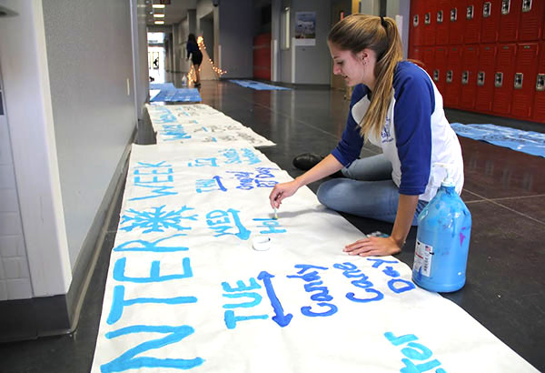"""Student Council member Adrianna Willeford paints a banner advertising """"Winter Week."""" The week will take place from Oct. 15-19 and will consist of spirit dress up days and holiday themed lunch games. """"I'm really excited because I love the holiday season and I hope that the student body is ready to participate in some really awesome spirit days,"""" Willeford said.   Photo Credit: Helen Abraha"""
