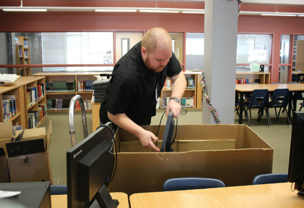 """Clark County School District (CCSD) Computer Technician Peter Ramirez unloads the box of Lenovo computer monitors. Ramirez, along with his co-workers, replaced the 32 Dell computers with Mac minis. """"The Mac minis are much faster and it's a newer generation of computers so the students will absolutely love it,"""" Ramirez said.  Photo Credit: Jen Chiang"""