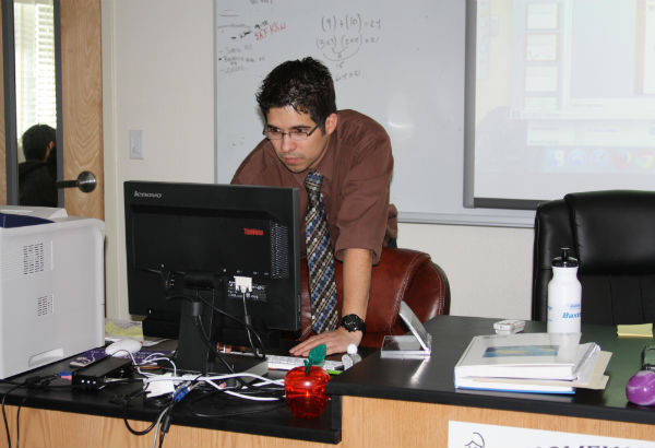 """Mr. Patrick Waddington sets up a PowerPoint presentation to start his lesson during his physics class. As a newly licensed teacher, Waddington plans on assigning hands-on assignments.""""I want students to see physics in everyday life, and I don't want them to be afraid of science, even if it is not their strongest subject,"""" Waddington said. Photo Credit: Acel Soriano"""