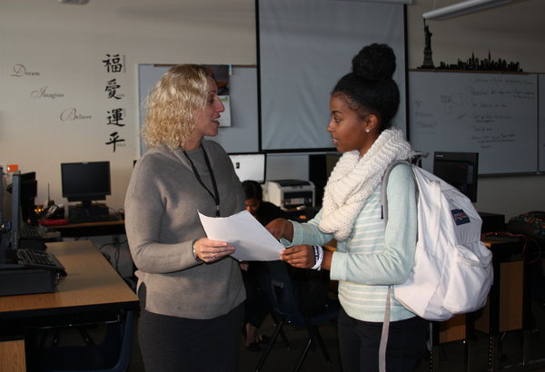 "Caption: Fitness Club adviser Ms. Linda Burns explains the requirements for joining the club to senior Amelinda Futsum. At the beginning of the year, the club was cancelled due to the lack of an adviser, but will have the first meeting of the school year on Jan. 23. ""Yoga will be the most interesting part for me. I've never done it before, but it seems like an activity that I would like,"" Futsum said. Photo Credit: Helen Abraha"