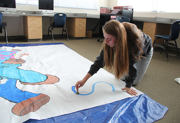 """Student Council member Zoey Kriethe creates a poster to ask someone to the Sadie Hawkin's dance on Feb. 17. The theme of the dance is """"GameOn!"""" and Kriethe incorporated the theme by painting a photo of Mario. """"I think it's really good that we're doing a Sadie's dance and a game night because more people are likely to come,"""" Kriethe said.  Photo Credit: Helen Abraha"""