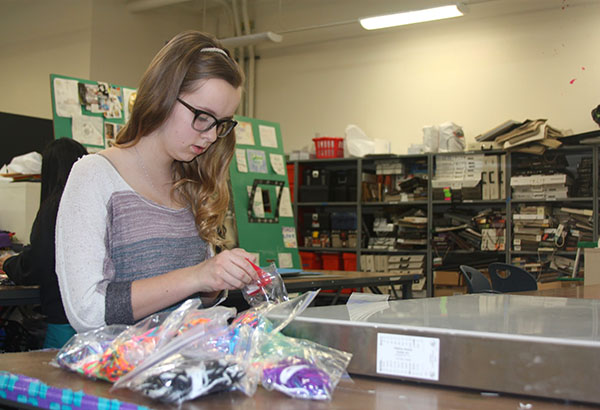 "Freshman Grace Lange fixes labels with instructions for the warm fuzzies prior to delivering them to students. StuCo started creating warm fuzzies on Jan. 5. ""I think the warm fuzzies are the coolest idea because it shows people care for others and it shows the idea that when you give love, you also receive love in return,"" Lange said. Photo Credit: Jorge Carrera"