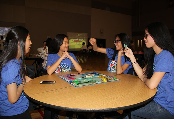 """Juniors Mary Allyn Maguddatu, Rachel Gomez, Angelica Mayor and Xueying Zheng engage in an exciting game of """"Sorry!"""". The four attended the sixth annual Sadie Hawkin's dance on Feb. 28. """"I really enjoyed Sadie's with my friends because we would go dance and then play the games,"""" Mayor said.  Photo Credit: Patricia Ascano"""