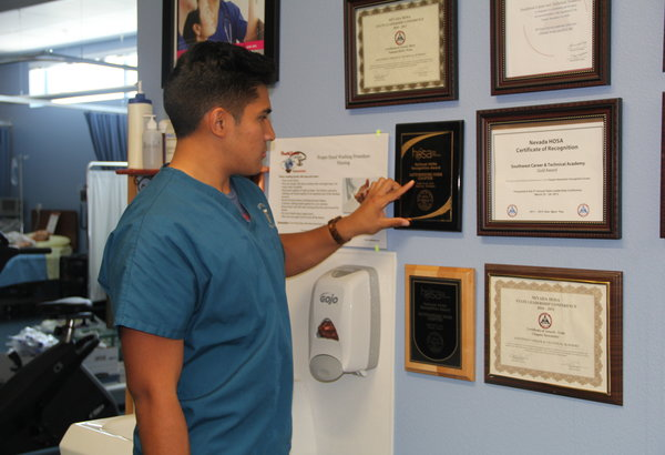 """Newly elected Nevada Post Secondary President Andres Caja reviews the plaques that were awarded to the chapter. 36 members qualified for nationals in Anaheim, California, and the chapter received many recognitions. """"I hope that I get to see all those who qualified for nationals in Anaheim, we need to support not only our chapter but also the state during the National Leadership Conference,"""" Caja said.  Photo Credit: Helen Abraha"""