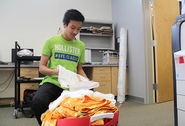 """Class of 2018 President Ramsey Gomez takes inventory of the Class of 2018 shirts that will be sold during the tie dye event on Apr. 14. The event will take place at the side the D building and proceeds will go toward the Class of 2018. """"I think that a decent amount of people will come because there are other items that they can purchase such as snacks, so they can have a good time tie dying while also having a good time with friends,"""" Gomez said.   Photo Credit: Acel Soriano"""