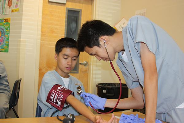 Kevin Dang assists Matthew Le in setting up his blood pressure cuff.