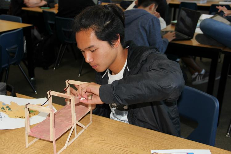 Sophomore Patrick Meneses paints a bridge for the civilization his group created.
