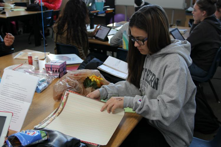 Sophomore Alise Ferrante flips through papers to find the right one for her project.
