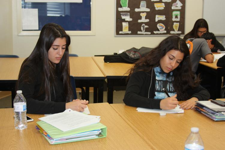"""Reading the packet along with the speaker helps juniors Janessa Montenegro and Crystal Menjivar understand the main idea of the story. """"I grew up with people that spoke Spanish, but my parents never taught me so I took it upon my self and learned by myself,"""" Montenegro said."""