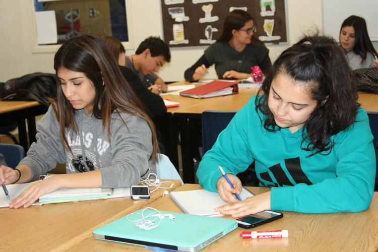 """Senior Julia Hernandez and junior Elizabeth Carrasco take in the words of the novela and try to interpret what it means. """"I learned Spanish when I was a baby so explain and understanding the novela came easy to me,"""" Hernandez said."""