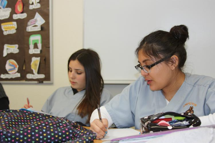 """Listening to a phone call and writing down what the caller says are sophomores Estefania Cabral and Paulina Grijalva. In this activity the students must listen the call and write each word down word for word. """"I learned that the Spanish language is such a beautiful language in that it can mean so many different things. The amount of detail in this story is incredible,"""" Grijalva said."""