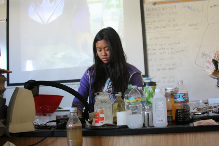"""Sophomore Kaitlan Gutierrez presents her demo turning milk into stone. """"I turned milk into stone by using simple materials such as milk and vinegar. When I let the certain substance sit out in room temperature for a couple of hours, the milk had succeeded into turning hard like stone,"""" Gutierrez said."""